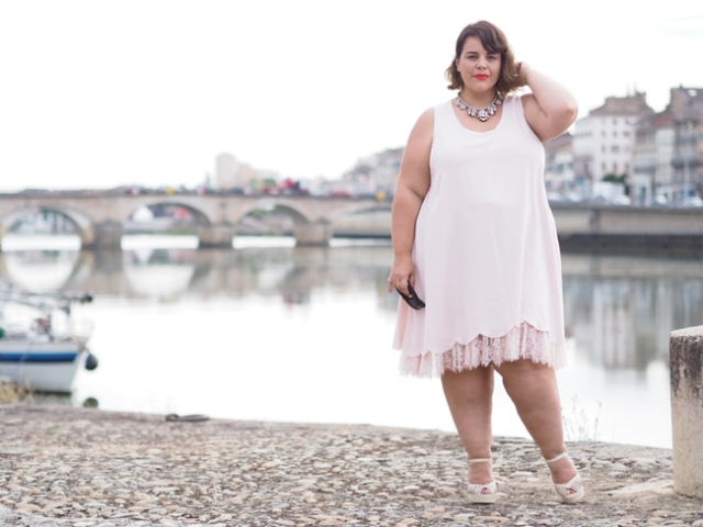 plus size outfit with gorgeous white dress with lace trim, standing in front of scenic river with bridge in france