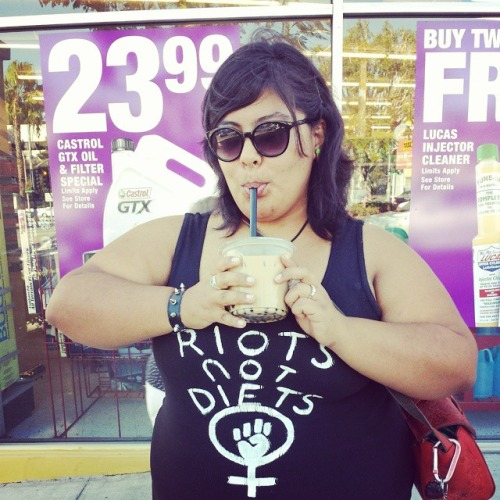"plus size woman drinking bubble tea and wearing ""riots not diets"" tank top"