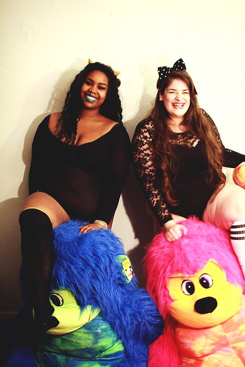 two plus size women in blakc bodysuits with giant colorful stuffed animals