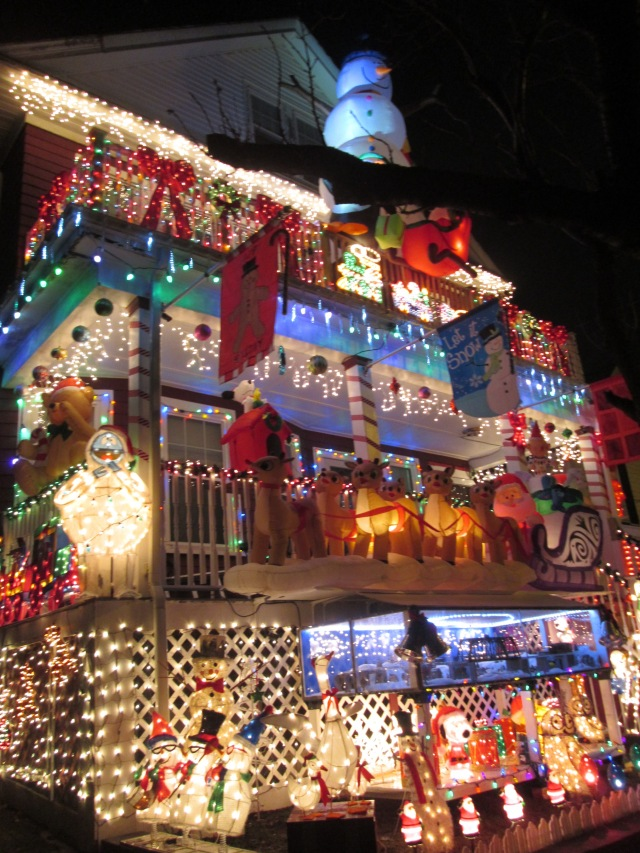 house with lots of christmas decorations including toy train and large snowman