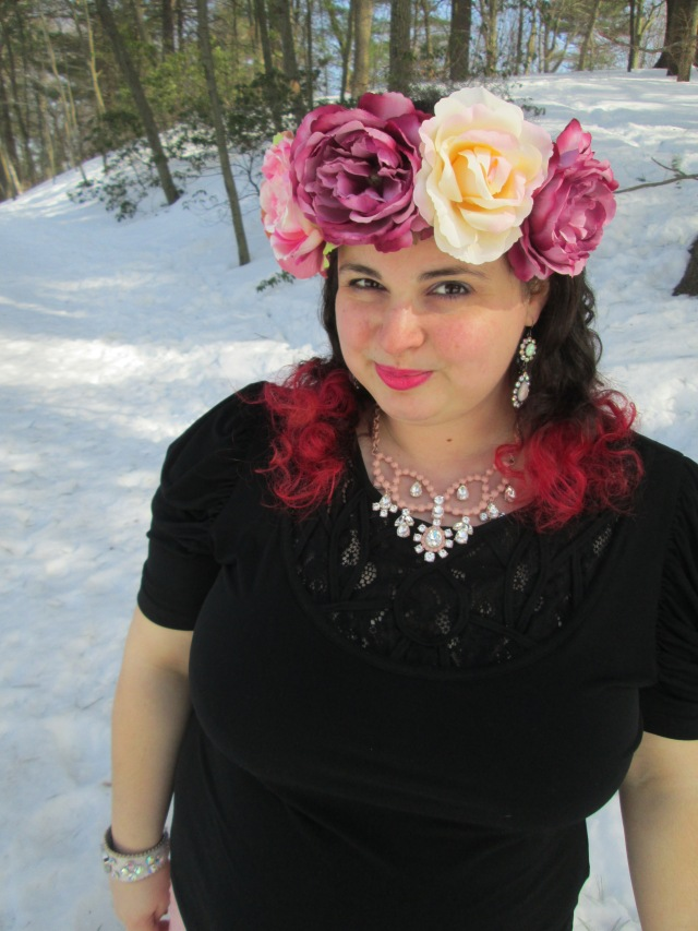 plus size outfit with black top, rhinestone necklace, and giant flower crown